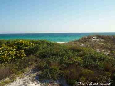 Emerald waters peek through the dunes