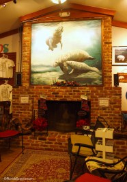 Manatee painting above cozy fireplace in gift shop